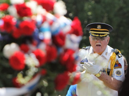 """A Richard M. Campbell Veterans Nursing Home honor guard member applauds after the end of the """"Star-Spangled Banner"""" at a Memorial Day ceremony Monday."""