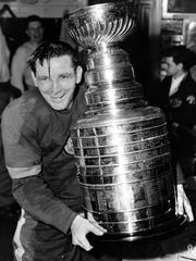 Captain Sid Abel of the Detroit Red Wings happily holds the Stanley Cup in the dressing room after his team's April 23,1950 victory over the New York Rangers.