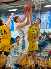 South Burlington's Patrick Mcmkin, center, shoots between BFA-St. Albans' Robert Kelly, left, and Micah Murray during a game last season.