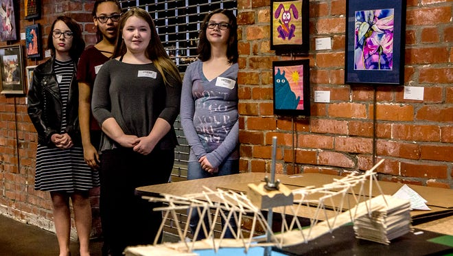 Students watch as the toothpick bridge they built for STEM Fest begins to break in half. Their bridge was able to hold 6.4 pounds of pressure before giving way to a 1/2 inflection.
