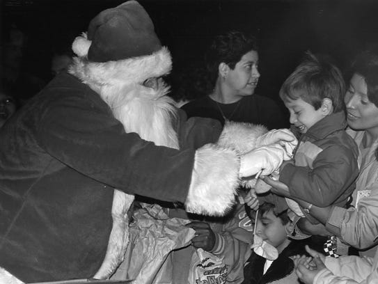 Santa passes out candy to a crowd of youngsters at the Central Fire Station on Dec. 20, 1988.
