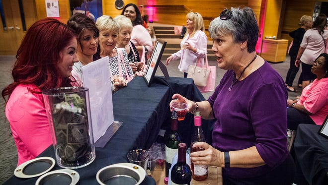 Attendees line up to sample wine provided by Friendly Package Liquors during the 2015 Wine, Dine & Unwind event at Minnetrista.