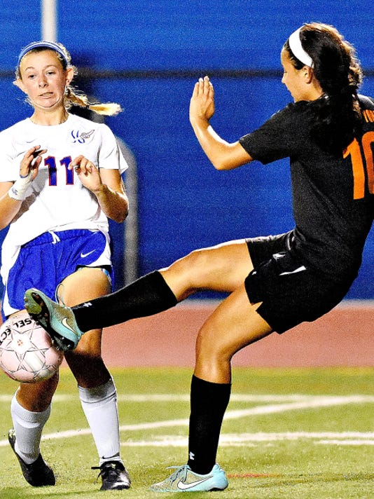 Spring Grove's Abby Erlemeier, left, reacts as Central York's Kennedy Little, right, kicks the ball during girls' soccer action in Spring Grove on Thursday. Central won the match, 1-0.