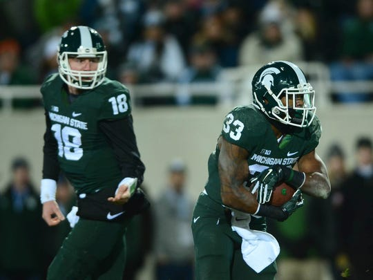 Michigan State RB Jeremy Langford runs with the ball as Connor Cook looks on.