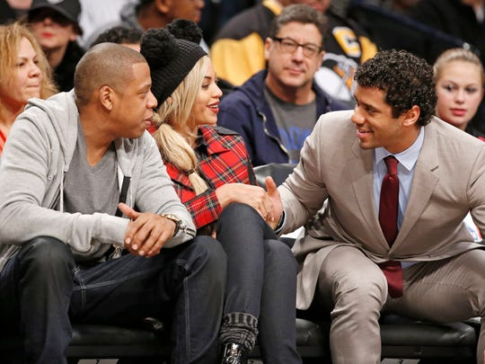 Seattle Seahawks quarterback Russell Wilson, right, says farewell to entrepreneur and musician Jay Z, left, and Jay Z's wife, singer Beyonce, after sitting court side with the entertainment couple watching the Philadelphia 76ers at the Barclays Center, Feb. 3, 2014 in New York.