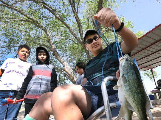 Saul Sanchez shows two bass he caught in an inlet to Ascarate Lake during a picnic day with brothers Nathan Espinosa, left, Aden Espinosa and Brandon Espinosa Thursday.