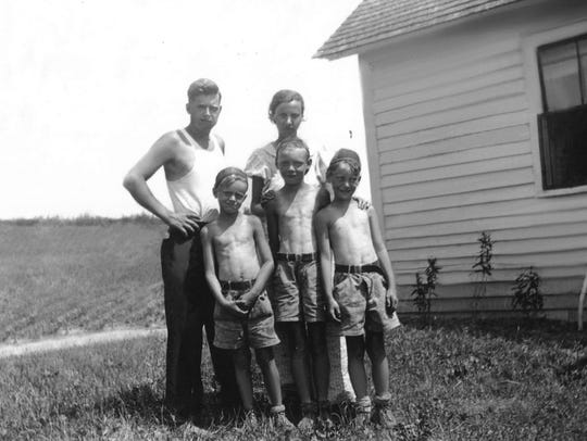 Albert Travis poses alongside his family. Back from