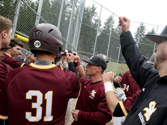 South Kitsap coach Marcus Logue (center) gets his team ready to take the field against Emerald Ridge in Puyallup on Tuesday, April 3, 2018.