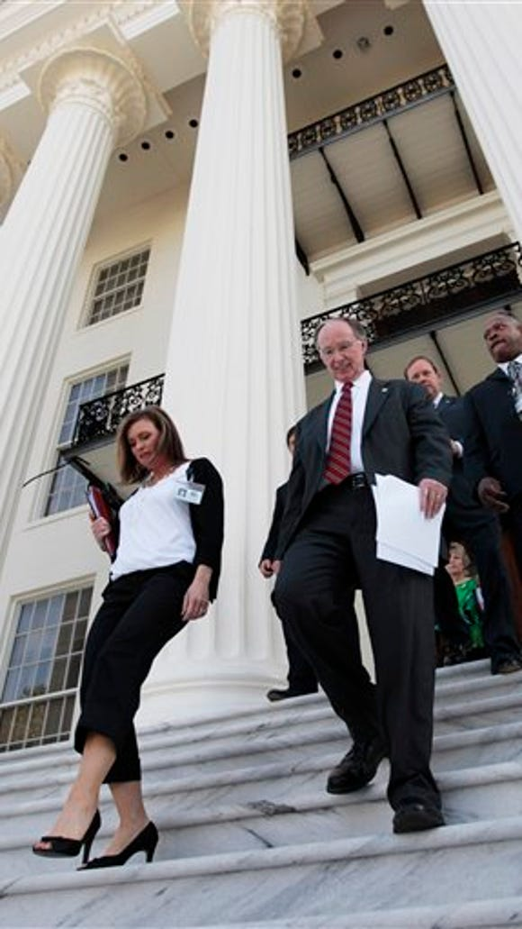 FILE -In this Tuesday, March 22, 2011 file photo Alabama Gov. Robert Bentley, center, arrives for a news conference at the Alabama Capitol in Montgomery, Ala. At left is Rebekkah Mason, Bentley's Communications Director. Bentley admitted Wednesday, March 23, 2016, that he made inappropriate remarks to his senior political adviser, Rebekah Caldwell Mason. Bentley said he did not have a sexual relationship with Mason, but he apologized to his family and Mason's for his behavior. (AP Photo/Dave Martin, File)