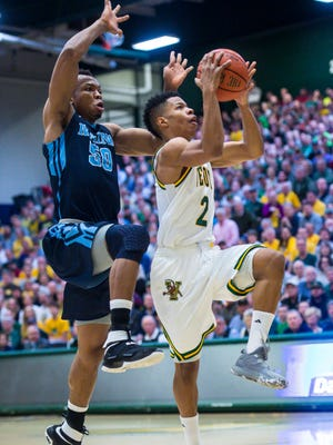 The University of Vermont's Trae Bell-Haynes, right, drives to the basket under pressure from University of Maine's Vincent Eze on Wednesday, March 1, 2017.
