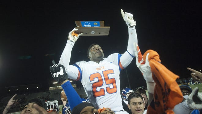 Millville's Zack Douglass , 25, raises the trophy after winning over Toms River North in the 2016 NJSIAA Football Championship game at Rowan University.