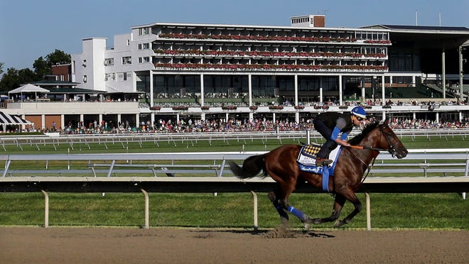In this July 31, 2015, file photo, people watch as Triple Crown winner American Pharoah with Jorge Alvarez up trains at Monmouth Park in Oceanport, N.J. With the opening of the thoroughbred season at Monmouth Park just days away, chief executive Dennis Drazin knows the track will be beating the odds by just breaking even. The coronavirus pandemic has idled the New Jersey Shore track for two months.