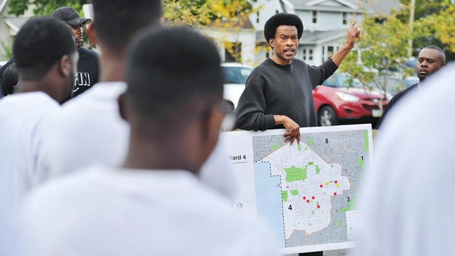 Event organizer Russ Neal, an Akron councilman, talks with cleanup volunteers before the Black-Out CommUNITY Day of Service in 2017.