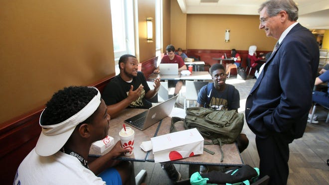 University of Akron President Gary Miller visits with a group of students in the student union on Oct. 1, his first day as president.