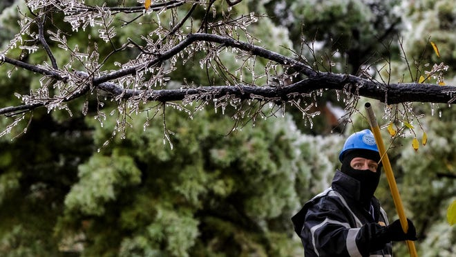 Crews work to knock the ice off the Survivor Tree at the Oklahoma City National Memorial & Museum in Oklahoma City, Okla. on Tuesday, Oct. 27, 2020, after a winter blast covered the state with ice.