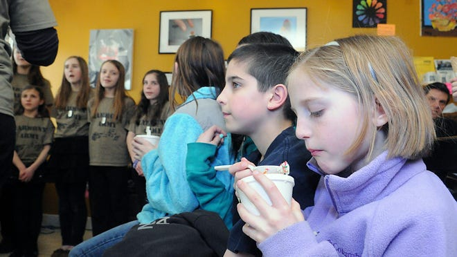 "Medway's Maura Thompson, pictured when she was 8 years old in 2013, digs into her cup of ice cream while listening to the perfromance by the ""Harmony Army"" during an ice cream social to benefit the Wounded Warriors Project at TC Scoops. Thompson scored a goal in the Medway field hockey team's win on Sunday."