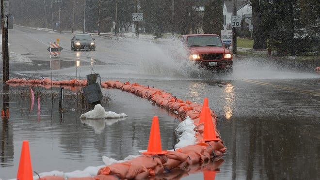 Motorists navigate the flooded state highway Wisconsin 47 in Keshena before officials closed the road three days ago.