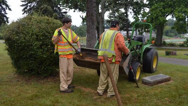 An inmate work crew from the Ottawa County Jail works on leveling headstones at Pilgrim Home Cemetery on Aug. 7, 2017.