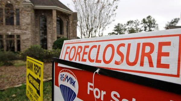 A 2009 file photo shows bank repo and foreclosure signs outside a foreclosed home in Houston.