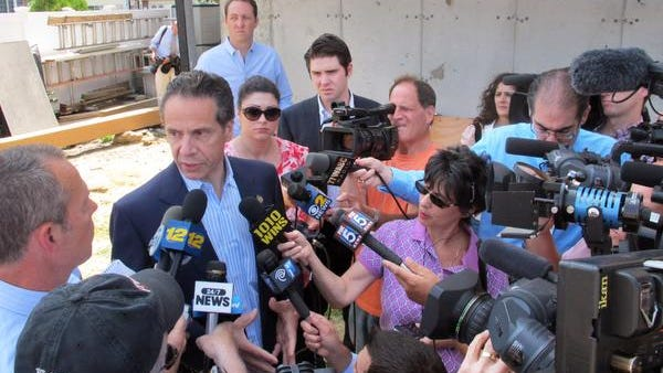 New York Gov. Andrew Cuomo, center left, is surrounded by the media in Freeport, N.Y. Cuomo was there to announce a new program to help victims of Superstorm Sandy, but ended up fielding questions about the political storm regarding his top his disbandment of the Moreland Commission on government corruption.