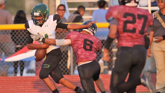 Shiprock's Quaid Shorty makes a defensive play against Newcomb's Nicolas Tsipai in the first quarter of Friday's game at Chieftain Stadium.