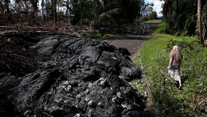 Hannique Ruder, a 65-year-old resident living in the Leilani Estates subdivision, walks past the mound of hardened lava while surveying the neighborhood Friday, May 11, 2018, near Pahoa, Hawaii. Kilauea has destroyed more than 35 structures since it began releasing lava from vents about 25 miles east of the summit crater.