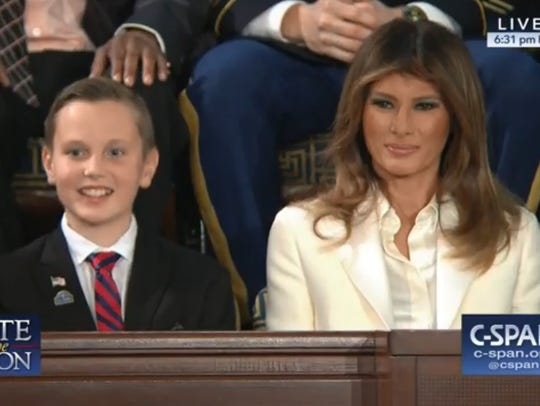 Preston Sharp sits next to First Lady Melania Trump
