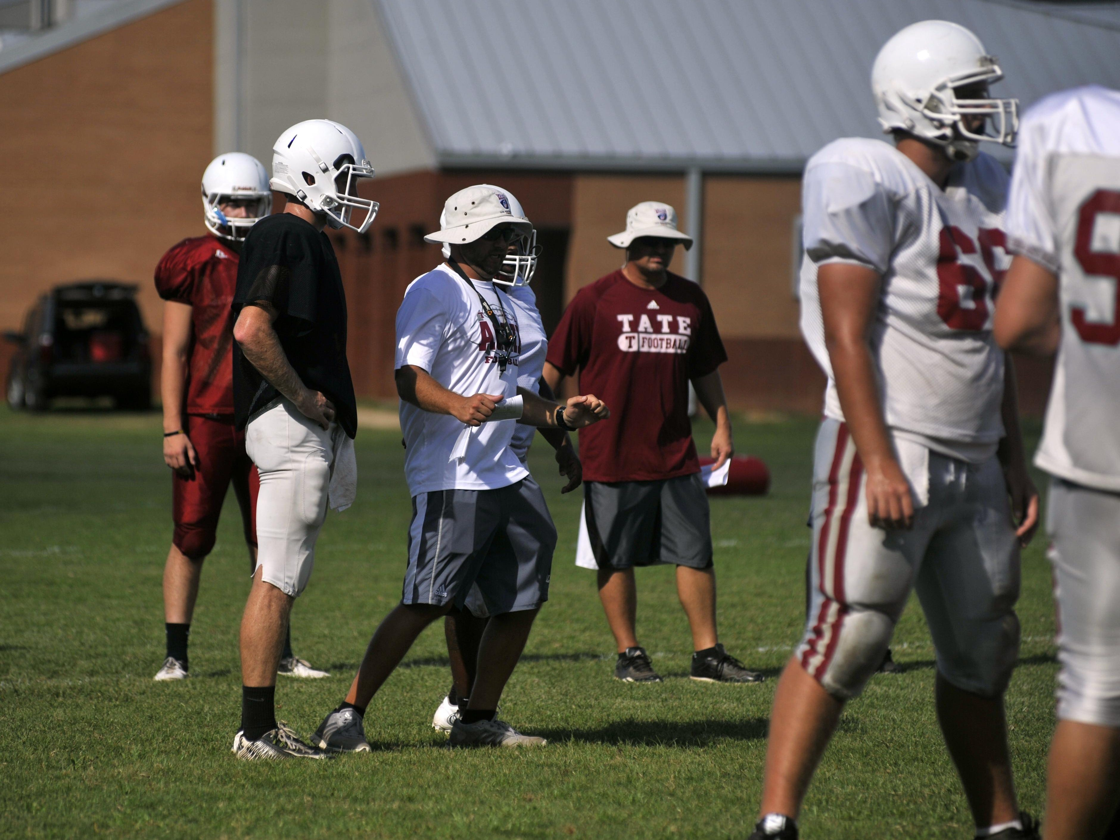 Tate head coach Jay Lindsey (center) instructs starting quarterback Jake Henry (black) during practice on Aug. 16, 2016.
