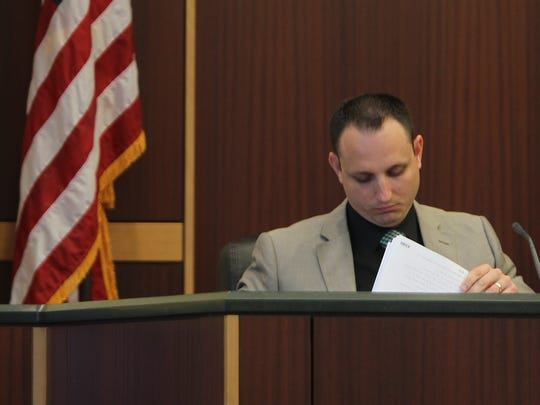 Lee County sheriff's Sgt. Michael Downs looks through the pages of an an affidavit which states accused co-conspirator Jimmy Rodgers said Mark Sievers offered him insurance money for the killing of his wife, Teresa.