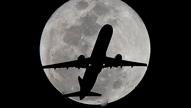 A commercial airliner crosses the full moon over Whittier, Calif., as it heads into the Los Angeles International Airport.