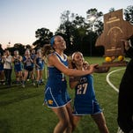 KCD players Danielle Fullerton (11) and Elise Ferguson (27) receive their trophy after defeating Sacred Heart, 10-9, in the 2015 Girls' Lacrosse State Championship at Sacred Heart Academy. May 21, 2015.