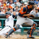 Detroit Tigers shortstop Andrew Romine (27) slides in safely at home behind Houston Astros catcher Jason Castro (15) in the fourth inning at Comerica Park.