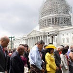 From left, Sen. Cory Booker, D-N.J., Rep. John Lewis, D-Ga., Sen. Joe Manchin, D-W.Va., Rep. Frederica Wilson, D-Fla., Sen. Charles Schumer, D-N.Y., and others gather on Capitol Hill in Washington, Thursday, in prayer to mourn the shooting victims of Emanuel AME Church in Charleston.