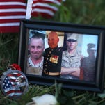 Photos of four of the five shooting victims are part of a memorial Saturday in front of a recruiting center in Chattanooga, Tenn.