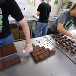 FILE - In this Sept. 26, 2014, file photo, smaller-dose pot-infused brownies are divided and packaged at The Growing Kitchen in Boulder, Colo. Edible marijuana products in Colorado may soon come labeled with a red stop sign as the state is finalizing work on new rules for the appearance of edible marijuana. A draft of those rules released Tuesday, Aug. 11, 2015, would require each piece of edible marijuana to be marked in the shape of a stop sign with the letters THC in the middle. The letters stand for marijuana's psychoactive ingredient. (AP Photo/Brennan Linsley, File)