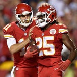 Alex Smith (11) celebrates teammate Jamaal Charles' touchdown run during a game against the Denver Broncos at Arrowhead Stadium on Sept. 17.