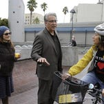 In this Wednesday, Oct. 28, 2015, photo, San Francisco Sheriff Ross Mirkarimi campaigns near a Mission District transit station as his wife, Venezuelan-born Eliana Lopez, left, listens in San Francisco. Only two incumbent San Francisco sheriffs have lost re-election in the last 60 years and Mirkarimi is facing a tough battle on Nov. 3 to avoid being the third. Thrust into the middle of the national immigration debate this summer, Mirkarimi is being outspent by an opponent garnering key endorsements and who seeks to capitalize on the incumbent's problems during his first four years in office.