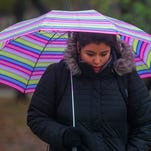 A cold rain falls as Alejandra Placid, a freshman from Storm Lake, walks to class at Iowa State University in Ames , Monday, Nov. 30, 2015. A winter weather advisory took place in many counties across central and northern Iowa calling for freezing rain, wintery mixes and possible snow fall.