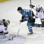 Minnesota Wild goalie Darcy Kuemper, left, blocks a shot by San Jose Sharks center Logan Couture (39) as Wild defenseman Jared Spurgeon, right, watches in the second period of their NHL hockey game Saturday in San Jose, Calif.