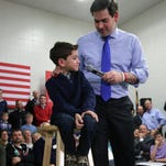 Dominick Rubio, 7, joins his father, Republican presidential candidate Sen. Marco Rubio, on stage during a town hall Thursday in Salem, N.H.