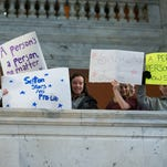 Students from Seton Catholic School in Lexington holds signs during a Right to Life rally at the Capitol Thursday.