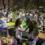 Pooja Santapuram, center, reacts to having colored powder thrown on her during the Holi celebration at Vanderbilt University, Saturday, April 9, 2016, in Nashville, Tenn. Holi is a Hindu color festival which celebrates the arrival of spring.