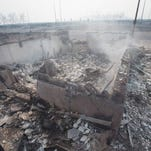 The foundation of a home smolders in a residential neighborhood destroyed by a wildfire on Friday in Ft. McMurray, Alberta.
