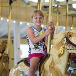 Kasey Murphy of Newark Valley rides the carousel at C.F. Johnson Park in Johnson City last summer.