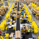 Workers packed boxes of orders at the Amazon Fulfillment Center in Jeffersonville, Ind.