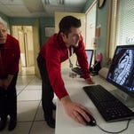 Tim Rose shows Janet Overman her CT scans at the James Graham Brown Cancer Center in Louisville.