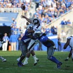 """UK DE Alvin """"Bud"""" Dupree hits Miss St QB Dak Prescott as he releases the ball, causing an interception, during the first half of the University of Kentucky football game against Mississippi State in Lexington, Ky. Saturday, October 25, 2014."""