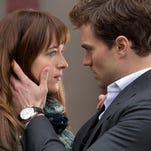 """Dakota Johnson and Jamie Dornan get hot and heavy in the big-screen adaptation of E.L. James' bestseller """"Fifty Shades of Grey."""""""