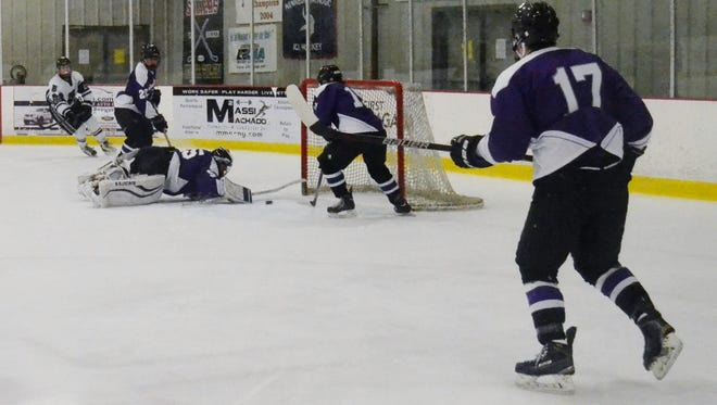 John Jay's Dom Protomastro (15) lends Indians goalie Taylor Isom a hand and sweeps a rebound away  Saturday during a 2-1 win over Brewster at Brewster Ice Arena.