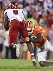 Clemson defensive back Jadar Johnson (18) tackles Louisville quarterback Lamar Jackson (8) during the 4th quarter on Oct. 1 at Clemson's Memorial Stadium.